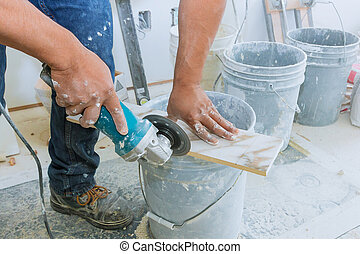 A construction worker cutting a tile using grinder