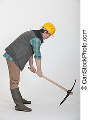 A construction worker digging with a pick axe.