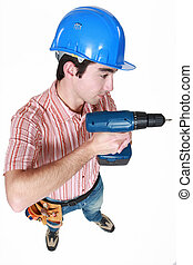 A construction worker holding a power tool