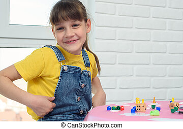 A contented nine-year-old girl looked into the frame, sitting at the table and playing a board game