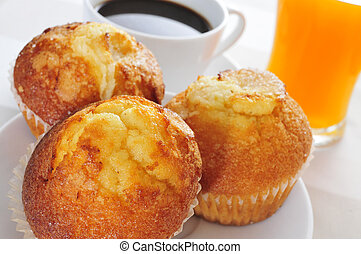 a continental breakfast formed by muffins, coffee and orange juice