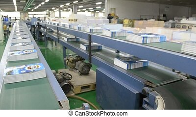 a conveyor bring un complete books to the next station