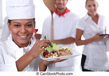 a cook holding a dish, a pizza cook and a waitress dressed...