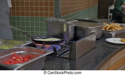A cook in the hotel restaurant fry an omelet with ingredients from vegetables. Eggs for breakfast in the buffet.