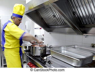 in a restaurant kitchen - a cook is stirring a dish in a...