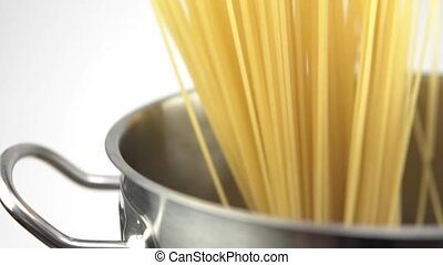 A cook puts down a spaghetti in a steel pan on a white background.