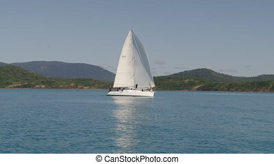 A cool white small sailboat - A moving shot of a sailboat...