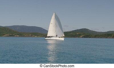 A cool white small sailboat - A moving shot of a sailboat...