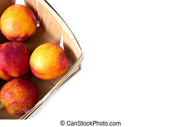 A corner of bushel basket with fresh picked yellow peaches, view from above, nice wallpaper