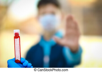 A Coronavirus blood sample in the hands. Crown virus outbreak. Epidemic time. Man on the background.