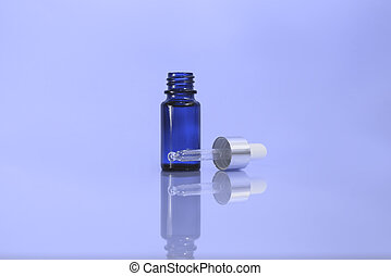 A cosmetic jar with glass dropper on the blue background.