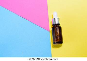 A cosmetic jar with glass dropper on the multi colored background.
