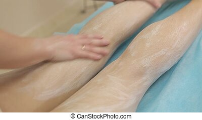 A cosmetologist smears women's legs with a cream and makes a...