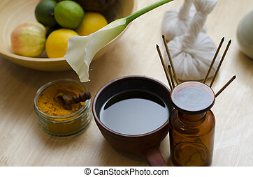 A countertop arrangement of ayurvedic turmeric spice, oil and massaging tools and an exotic flower used in Ayurveda massage.