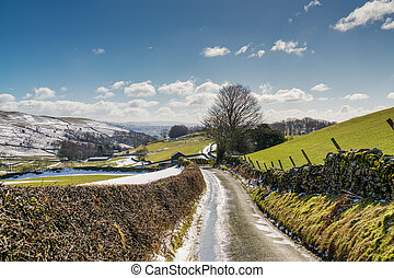 A country lane leading through snow spattered farmland.