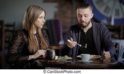 A couple, a man and a woman in a modern restaurant, have lunch or dinner. A man and a woman enjoy food and have a social conversation. Husband and wife are happy in marriage, they have a day off