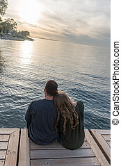 A Couple At Sunset By The Water