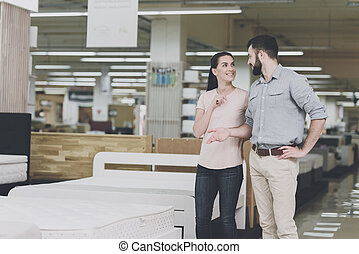 A couple chooses a mattress in the store. A woman points at one of them. A man is standing by