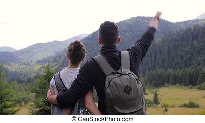 A couple climbing a mountain range, raise their hands up for...
