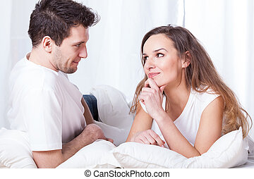 A couple contemplating in bed - A man and a woman lying in ...