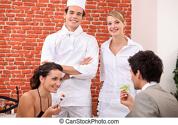 a couple dining at restaurant, a cook and a waitress behind them