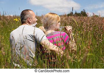 couple enjoys an e-cigarette in the nature
