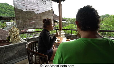 A couple have breakfast together around their terrace table, young family having fun on the beautiful asian country with wonderful green nature, holidays concept outdoors