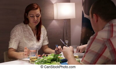 A couple having dinner at the table and talking
