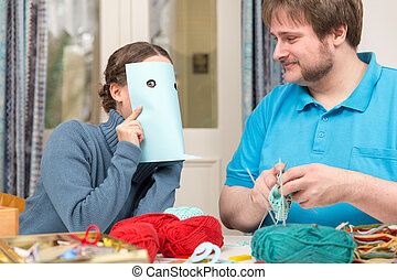 a couple having fun on doing crochet