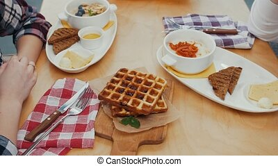 A couple having lunch - waffles and other food on the table