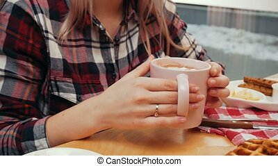 A couple having lunch - young woman drinking coffee