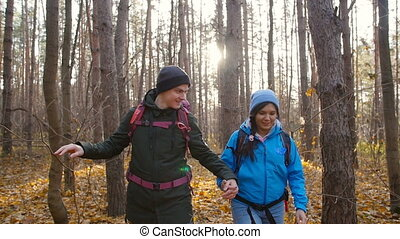 A couple hikers Hiking with backpacks in autumn forest . Concept of active rest