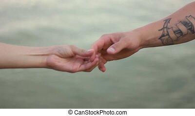 a couple holding hands closeup
