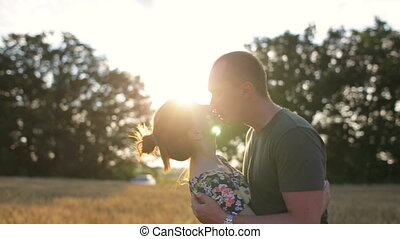 A couple hug, kiss and then walk in a wide open golden field at sunset