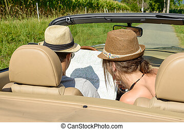 a couple in a convertible, look at a map