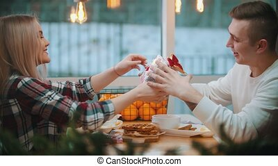 A couple in cafe - a woman gives her boyfriend a christmas gift