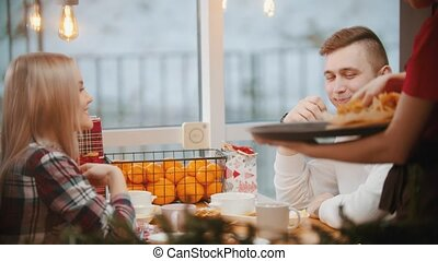 A couple in cafe having a lunch and talking to each other - waiter brings them an order