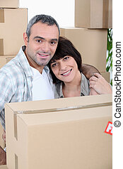 a couple in front of a pile of cartons
