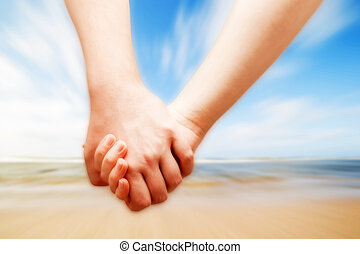 A couple in love hand in hand on the sunny beach