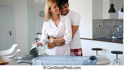 A couple in love ironing clothes - Couple in love ironing ...