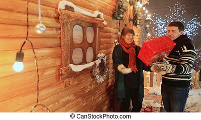 A couple in love sit on the background of a wooden fairy house toss a red gift. Christmas and New Year theme