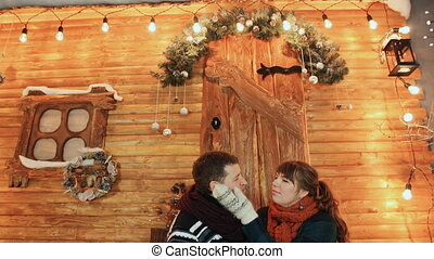 A couple in love sit on the porch of a wooden fairy-tale house and enjoy each other. Christmas and New Year theme.
