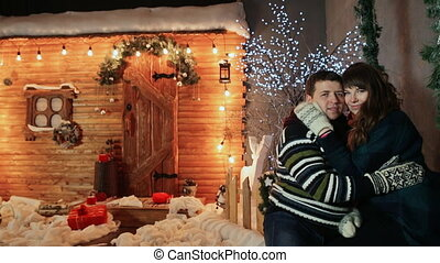 A couple in love stand on the porch of a wooden fairy-tale house and enjoy each other and closing his eyes. Christmas and New Year theme.