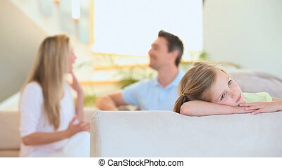 A couple in the background argue on the couch while a girl...