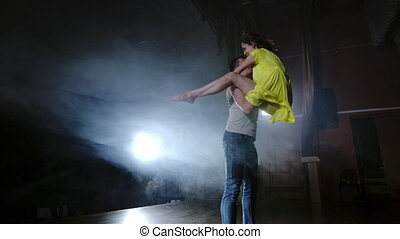 a couple is dancing doing acrobatic tricks on stage in smoke...