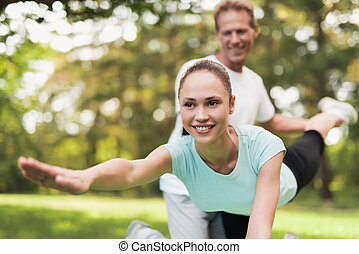 A couple is engaged in sports in a warm summer park. A man helps a woman stretch.
