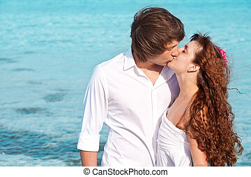 A couple is kissing on the beach - A beautiful couple is...