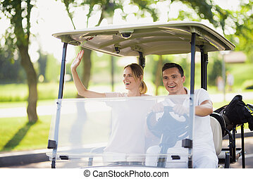 A couple is sitting in a white golf cart. A man is driving, a woman is sitting by and welcomes someone