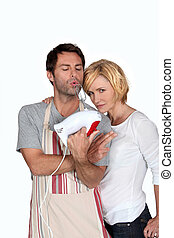 A couple jesting in kitchen