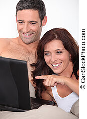 a couple laughing behind a computer